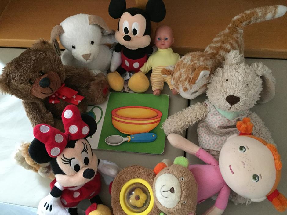 Unterschiedliche Stofftiere sind um ein Frühstücksbrettchen für Kinder gruppiert.