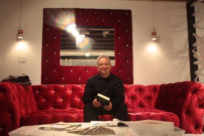 Achim Albrecht sitzt auf einem rotem Sofa und freut sich auf die Lesung.
