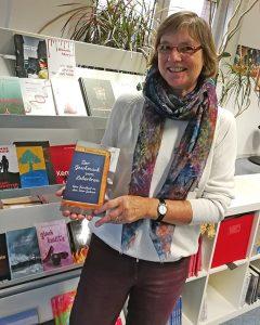 Cornelia Ertmer steht vor einem Bücherregal im Verlag und hält ihr Buch in den Händen.