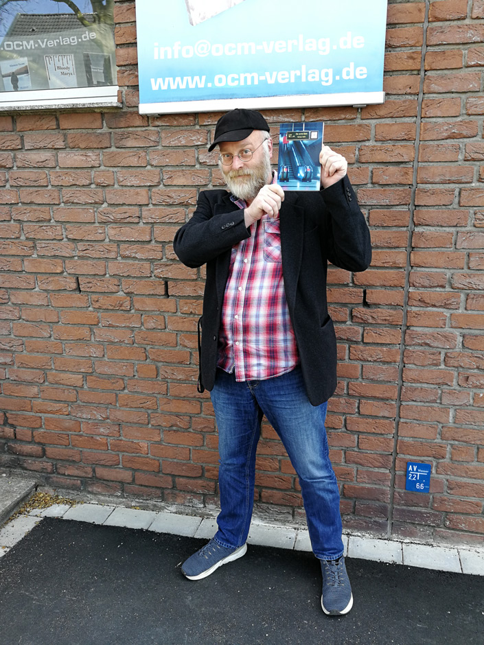 """Buchübergabe: Markus Veith mit seinem neuen Buch """"Die erste Bahn"""" im Freien, vor der Haustür des OCM Verlags. (2021)"""