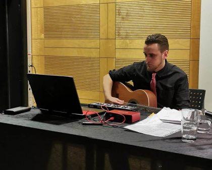 Ein Man sitzt an einem Tisch und spielt Gitarre.