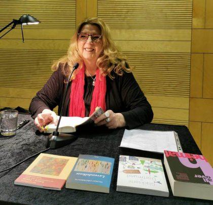 Sigrid Drübbisch sitzt an einem Tisch in der Stadt- und Landesbibliothek Dortmund und hält ihren neuen Krimi Mord-Art in der Hand.