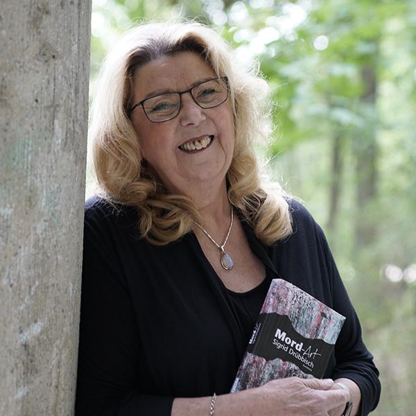 Die Autorin Sigrid Drübbisch lehnt sich an einen Baum und hält ihren Krimi Mord-Art in den Händen.