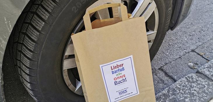 Eine Papiertüte lehnt am Reifen eines geparkten Autos.